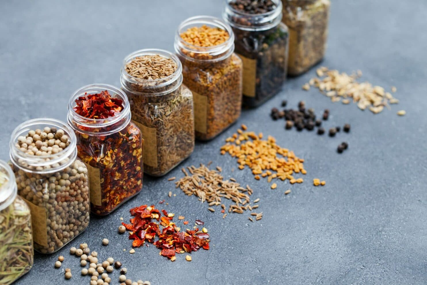 Assortments of spices, white pepper, chili flakes, lemongrass, coriander and cumin seeds in jars on grey stone background. Copy space